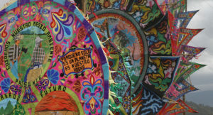 photo of colorful drawings of earth and people working the earth with statement that the planet is our home
