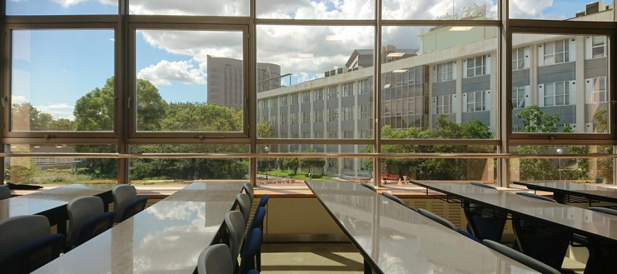 Empty college classroom with long desks and many chairs, large windows in the background showing bright skies with some clouds
