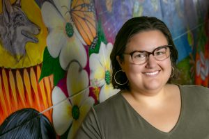 Photo of Cecilia Marquez with a brightly painted mural in the background