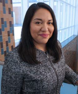 Photo of Perla Guerrero wearing a grey and black blazer with a window in the background
