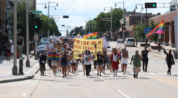 """Protestors marching down the middle of the street holding Pride flags and a banner that reads """"Pride-BLM Solidarity"""""""
