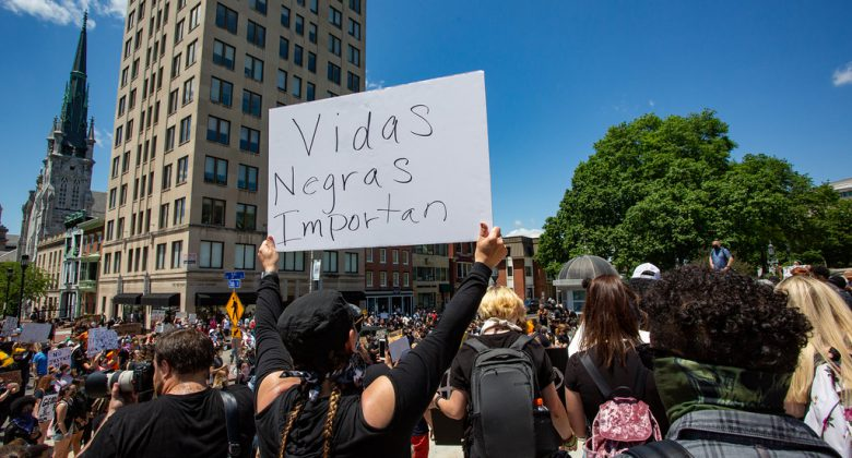 """Crowd in a large urban city center with a protestor holding a sign reading """"vidas negras importan"""""""