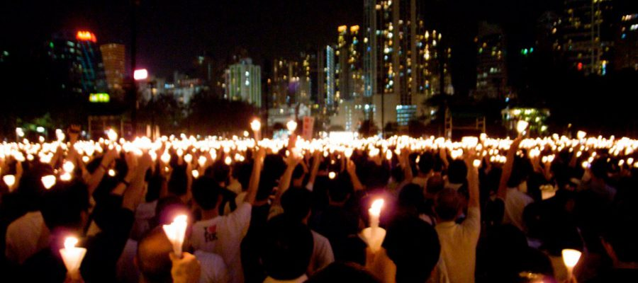 Crowd of people gathered in an urban area for a candlelight vigil